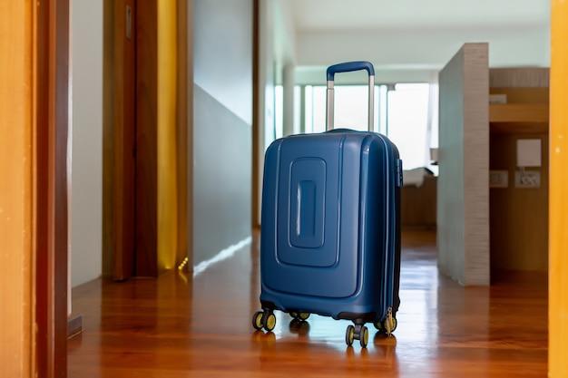 Синий чемодан в светлом гостиничном номере с коричневыми деревянными деталями. копировать пространство