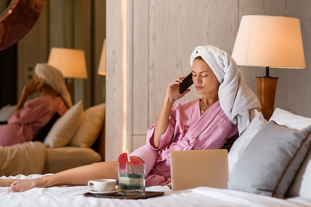 Красивая женщина с полотенцем на голове, разговаривает по телефону в спальне у себя дома. утренняя рутина.