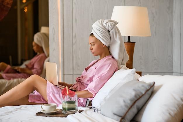 若い女性は彼女のラップトップでモダンな寝室のインテリアにベッドに座って作業します。モダンなベッドルーム。仕事の後のリラクゼーション。