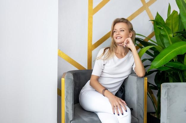 居心地の良いスタジオで植木鉢の近くの肘掛け椅子に座ってポーズブルーマニキュアで美しい笑顔金髪
