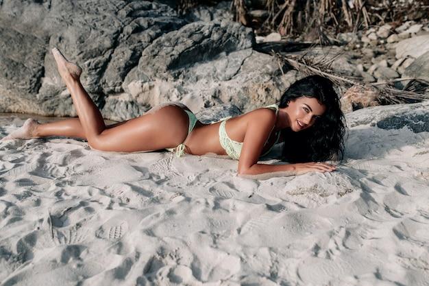 ニットの水着に身を包んだ魅力的な笑顔を持つ非常に美しいブルネットは、熱帯のビーチの砂に日焼けします