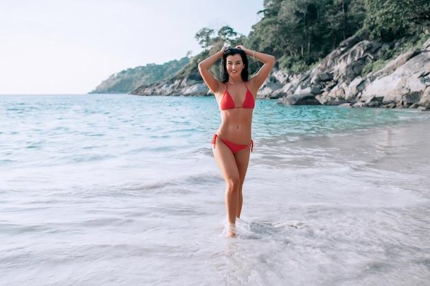 海のビーチでセクシーな赤いビキニ立っての美しい若い女性