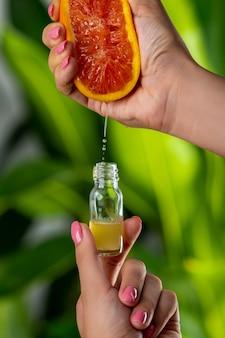 クローズアップ:女性の手がガラス瓶にグレープフルーツジュースを押します。自然化粧品のコンセプト