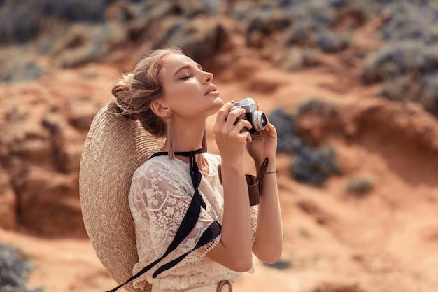 Модное изображение удивительной белокурой женщины с ветреными волосами, позирующими с ретро камерой, наружной на закате.