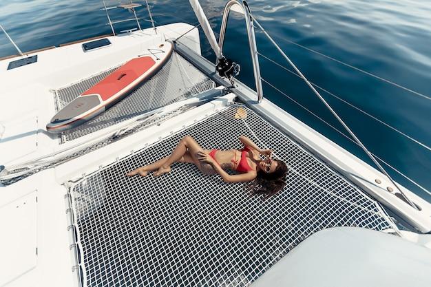 贅沢な休暇。ヨットの上に横たわる赤いビキニでセクシーな女の子、熱帯の海でリラックスします。