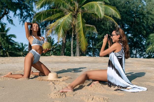 白人女性は、ビキニでココナッツカクテルビーチで彼のアジアのガールフレンドを撮影します。トロピカルリゾート。友達との休暇。
