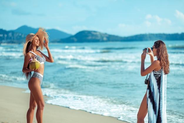 Две улыбающиеся молодые подруги в бикини и пьют кокосовый коктейль во время загара на тропическом песчаном пляже во время отпуска