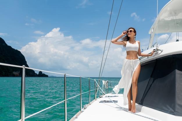 立っている長い髪の美しい少女は、白いスカートとビキニでヨットを弓します。