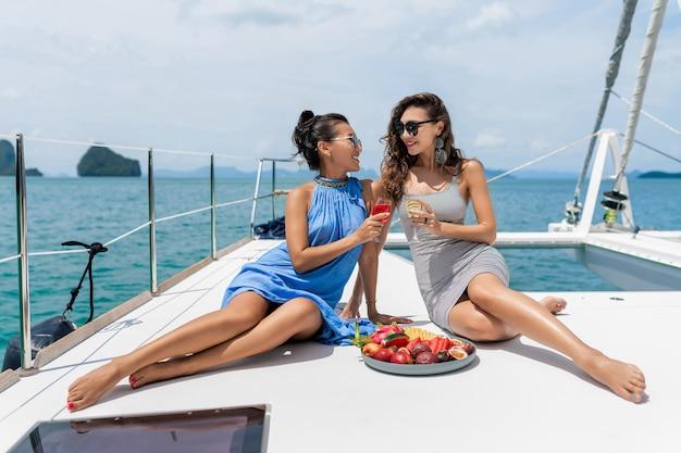 Подруги отдыхают на яхте. две девушки празднуют день рождения на яхте. красивые девушки пьют шампанское и едят тропические фрукты.