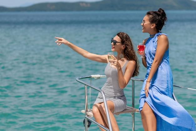 Подруги отдыхают на яхте. две девушки празднуют день рождения на яхте. красивые девушки пьют шампанское.