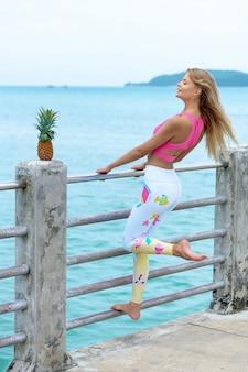曇り空に立っている桟橋でパイナップルでポーズ甘い女性を再生します。現代のスポーツ服