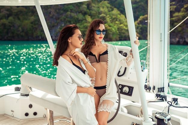 二人の女の子がヨットを走っています。夏のクルーズヨット。海でヨットで旅行する友人。ヨットの休日。背面図