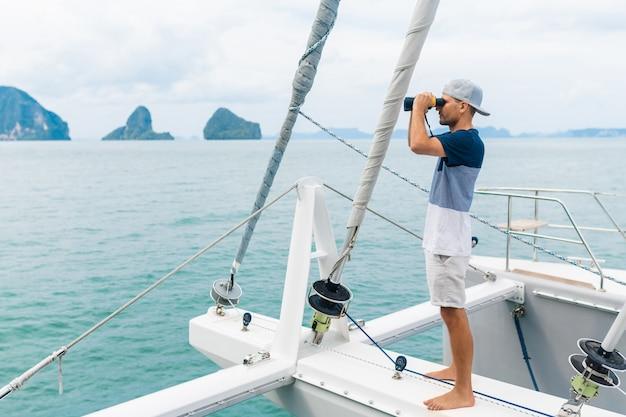双眼鏡で見ている若い男のヨット。旅行とアクティブな生活。