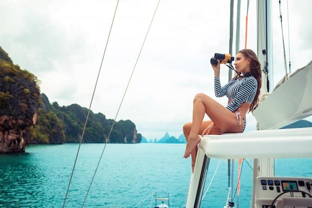 高級女性の手で双眼鏡でポーズします。ヨットでファッションストライプビキニを着ているモデル。美しい自然