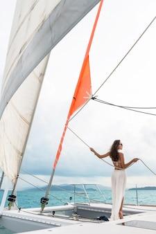 豪華な旅行ヨット。海のセーリングヨットで晴れた日を楽しむ若い女性。