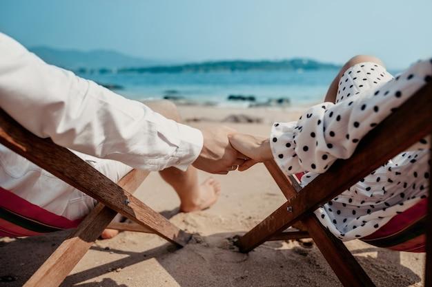 Любовь - романтическая пара, держась за руки на пляже в закат в то время как сижу лежаки