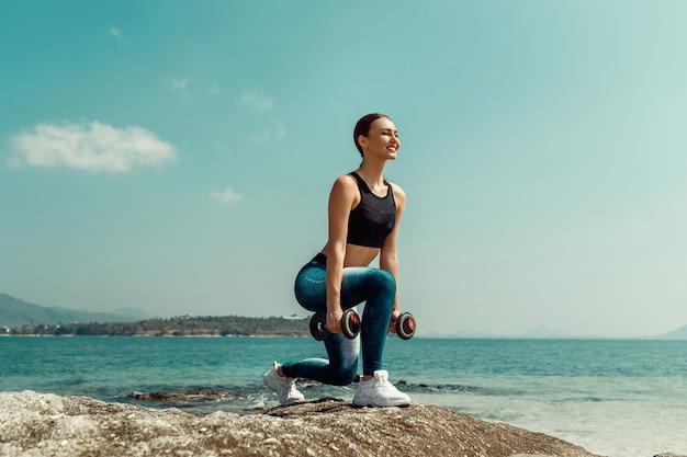 ダンベルと夏のビーチで完璧なボディトレーニングを持つ少女。スポーツ、フィットネス、運動、ダイエット。