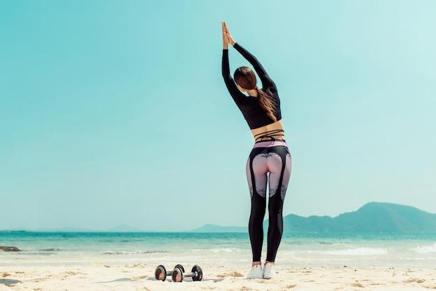 美しい女性は、晴れた日に海でヨガを練習します。女性はストレッチ体操を行います。砂に横たわっているダンベル。背面図