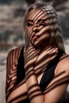 ジャングルミューズジャングルシーンで美しいファッションモデルを閉じます。熱心な目が太陽の光を探し、顔に影が落ち、暖かく生き生きとした雰囲気を作り出していると考えます。