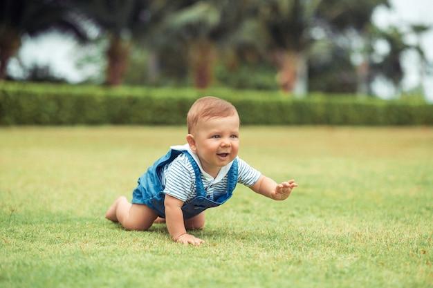 親にポートレートかわいい赤ちゃんクロールを閉じます。家族の屋外レクリエーション。小児発達。