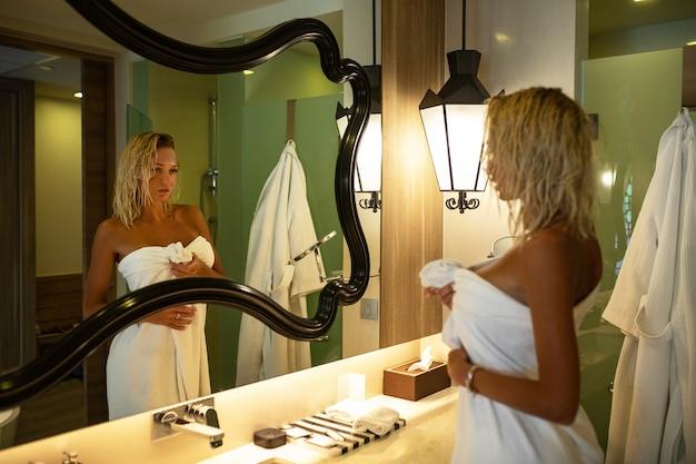 魅力的な女性は彼女の頭の上とバスローブで白いタオルで金髪が鏡で浴室に立っています。彼女は肌に触れて微笑みます。美しい白い歯。スキンケア 。