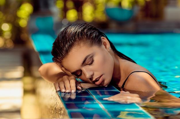 目を閉じてプールの水で横になっているファッションストライプ水着で日焼けした美少女。スパとリラクゼーション。夏休み。タイ