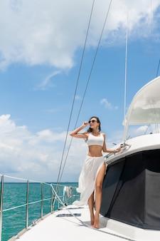 Молодая красивая девушка с длинными волосами стоит на носу яхты в белой юбке