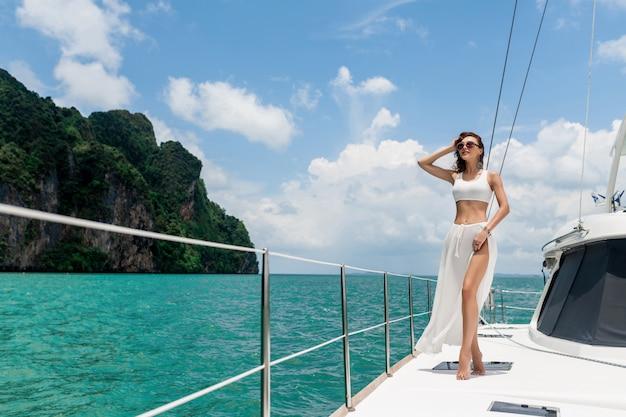 白いスカートでヨットの船首に立っている長い髪の美しい少女