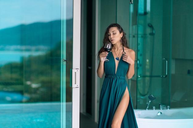赤ワインのガラスを保持している大規模な青い装飾と美しいイブニングドレスに立っている間ポーズセクシーなブルネット