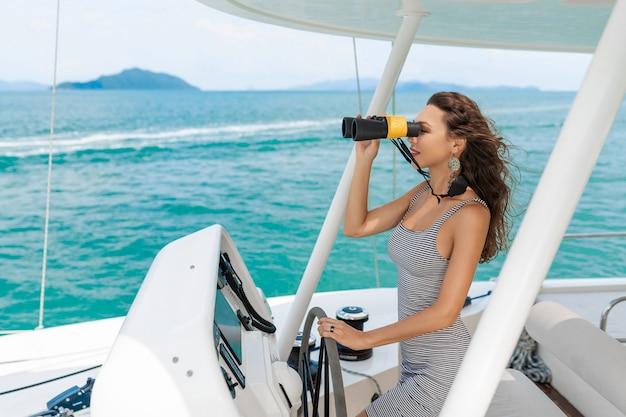 縞模様のドレスを着て、ヨットの上で双眼鏡を保持しているモデル