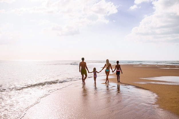 Большая семья, взявшись за руки и стоя возле моря. летний отпуск