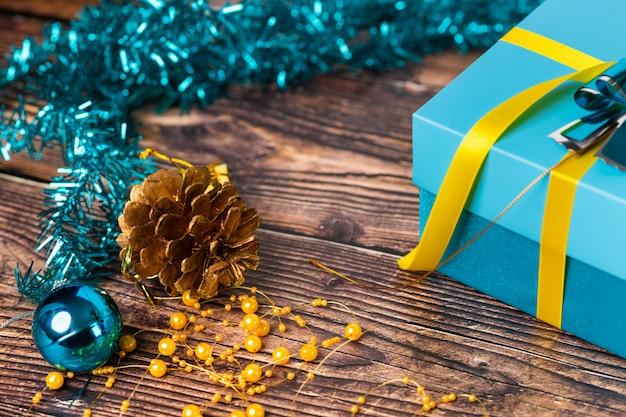 閉じる。青い包装紙に包まれた贈り物の隣にある木製のテーブルにある小さな黄金のモミの実