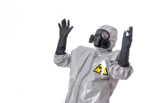 Человек позирует в сером защитном костюме с желтым знаком радиации, с защитным противогазом