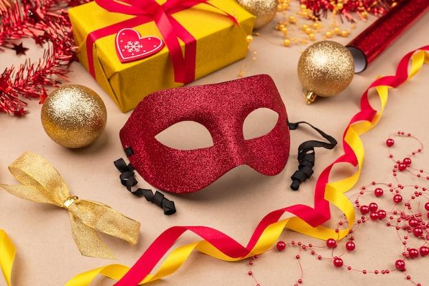 Праздничное настроение. подарки упакованы в желтую подарочную коробку, завернутую в красную ленточку, рулоны подарочной упаковки, красную маску-маскарад, желтый атласный бант, новогодние шары. крупный план.
