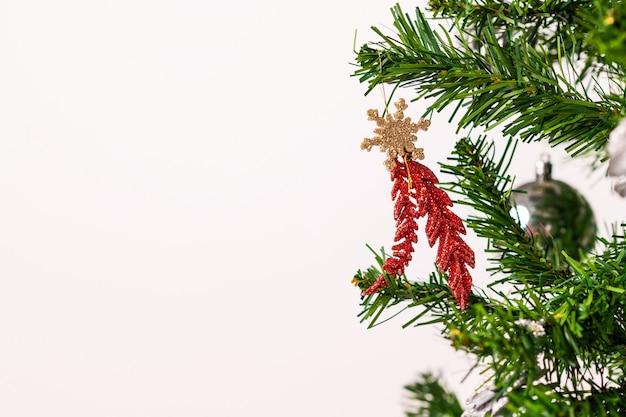 Новогоднее красное блестящее украшение расположено на ветке елки