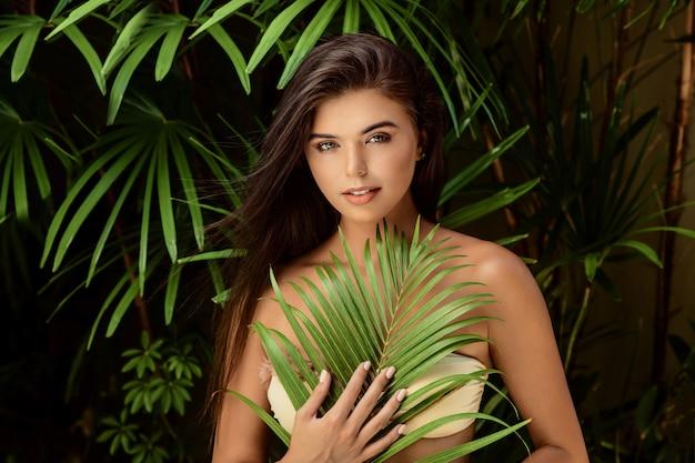自然に大きな緑の葉を持つ若い笑顔ブルネットの女性