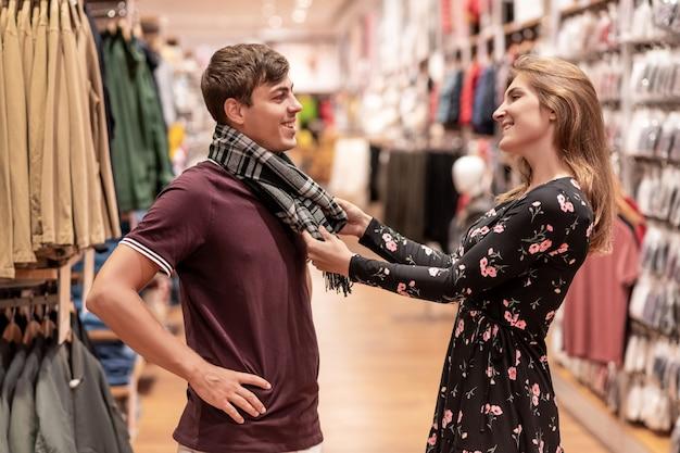 Красивая молодая пара позирует стоя посреди торгового зала.