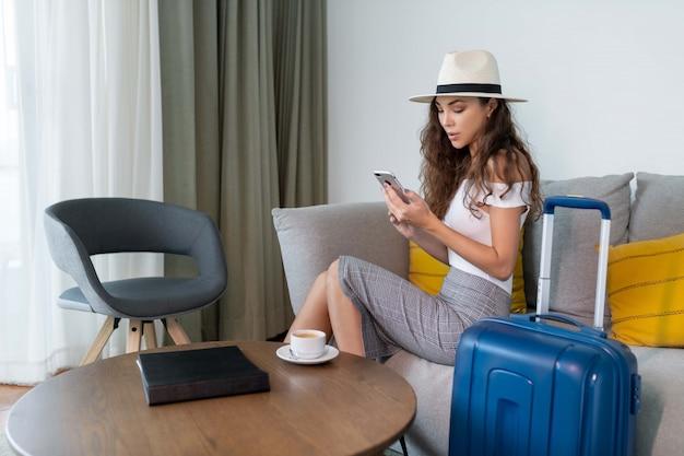 ソファの上の電話に座ってポーズスカートと白いトップの帽子のかわいいブルネット