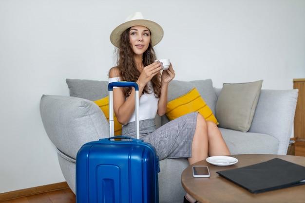 巻き毛のかわいいブルネットは明るい帽子のソファに座って、青いスーツケースとコーヒーテーブルの近くのコーヒーカップでポーズ