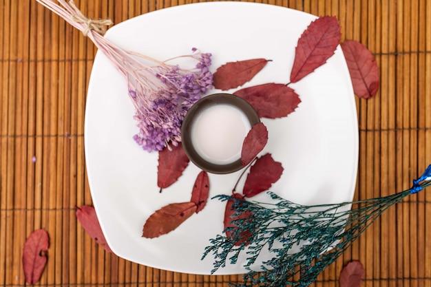 マットの上にある白い皿の上に、ミルクとラベンダーと赤の木の花びらの小枝が入った粘土のカップがあります