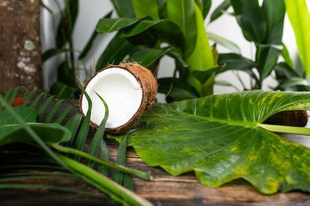 Раскрытый кокос лежит на деревянном столе среди зеленой листвы