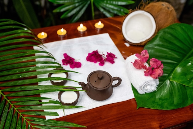 Чайная церемония расположена на белом махровом полотенце со свечами, цветами кокоса