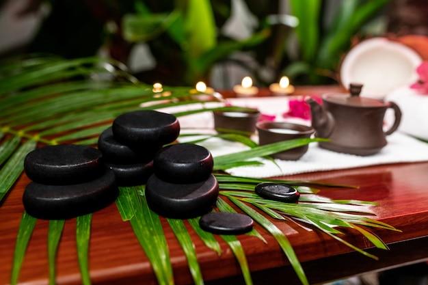 Аксессуары для чайной церемонии, расположенные на белом махровом полотенце со свечами, цветами, кокосами и каналами для стоунтерапии