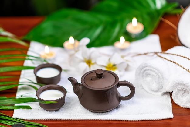 Аксессуары для чайной церемонии расположены на белом махровом полотенце со свечами и белыми цветами