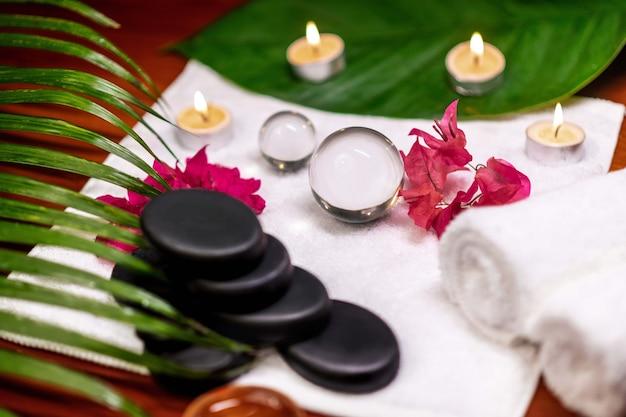 Камни для лечебного камня расположены на махровом полотенце, рядом с которым находятся свечи и белые шары для украшения и веточка цветов