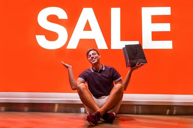 言葉販売で大きなオレンジ色の看板の近くに座ってポーズをとって、彼の手で購入するとパッケージを上げる若い男の笑みを浮かべてください。喜びの感情。ビッグセール。割引。ブラックフライデー。