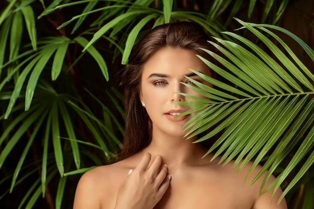 大きな緑の葉と若い笑顔ブルネットの女性、スパケアの人々の概念をクローズアップ