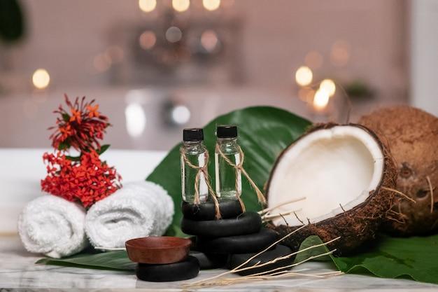 Два масла для ароматерапии стоят на камнях для лечебного камня, рядом с которыми находятся крученые полотенца, два кокоса, лежащие на зеленых листьях и разноцветные цветы, и горящие свечи на фоне ванны.