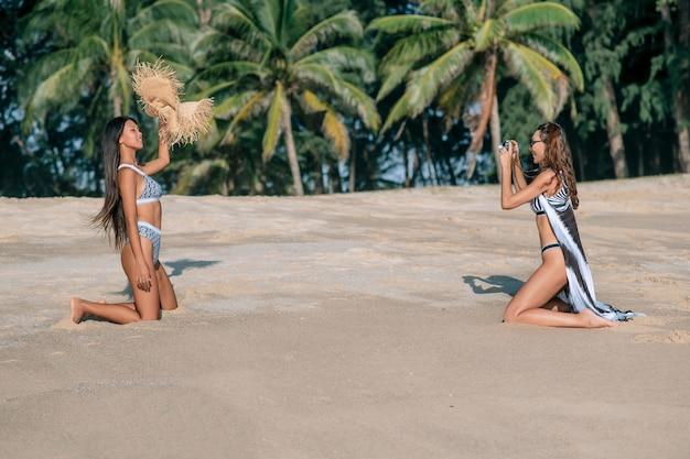 白人の女の子はビーチでビキニと麦わら帽子で彼のアジアのガールフレンドの写真を撮ります。トロピカルリゾート。友達との休暇。