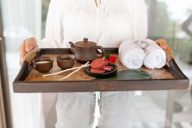 クローズアップ:手にトレイとコーヒーとクッキー、タオル、装飾、中国のティーポットを持つ少女。